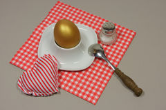 Golden egg in an egg cup on a red patterned napkin. With spoon and salt shaker Stock Image