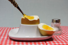 Golden egg in an egg cup on a red patterned napkin. With spoon and salt shaker Stock Photos
