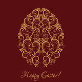 Golden egg with floral ornament on red Stock Photos