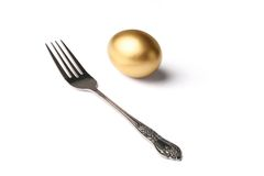 Golden egg and fork Stock Photos