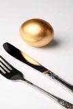 Golden egg and fork. Concept of Making Money Royalty Free Stock Photos