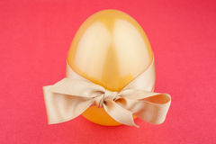 Golden egg with gift bow Stock Photography