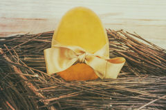 Golden egg with gift bow. In wooden nest, vintage postcard style Stock Photo
