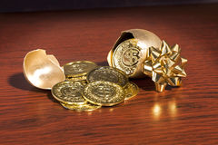 Golden Egg Gifts. A golden egg cracked open with gold coins coming out Royalty Free Stock Photography