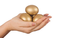 Golden egg in the hand Stock Photos