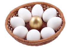 Golden egg and jast eggs in wicker bowl on a white Royalty Free Stock Images