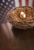 Golden Egg in Nest with American Flag Reflection on Table Royalty Free Stock Images