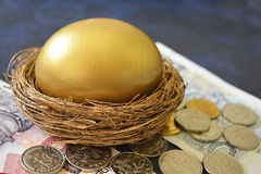 A golden egg in nest, banknotes and coins Stock Photography