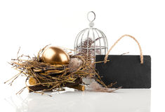 Golden egg in nest with blackboard with space for text Royalty Free Stock Photo