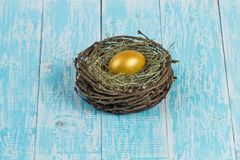 Golden egg in a nest. Chicken egg in a nest on a golden background decorated in the style of Provence Stock Photography