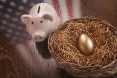 Golden Egg, Nest and Piggy Bank with American Flag Reflection. Golden Egg in Nest and Piggy Bank with American Flag Reflection on Wooden Table Royalty Free Stock Photo