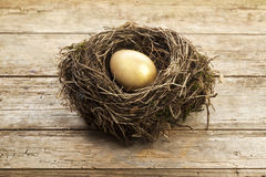 Golden egg in nest. On vintage wooden background Royalty Free Stock Image