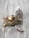 Golden egg. In nest, on wooden background stock image