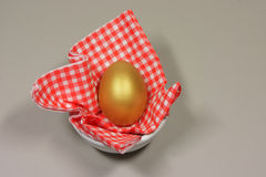 Golden egg patterned napkin. Golden egg in a patterned napkin Royalty Free Stock Photography