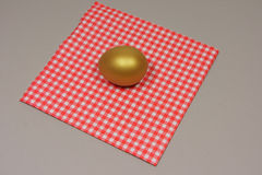 Golden egg on a patterned napkin. Red royalty free stock images
