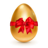 Golden egg with red bow Royalty Free Stock Images