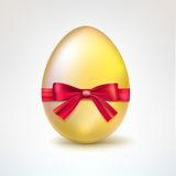 Golden egg with red bow. Royalty Free Stock Images