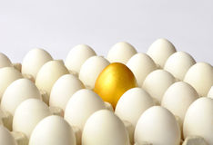 Golden egg among white eggs Stock Photo