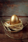 Golden egg on wooden table in  straw nest Royalty Free Stock Photography