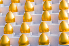 Golden eggs. Many gold eggs on a white stairs Royalty Free Stock Images