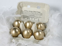 Golden eggs. Box of golden eggs Royalty Free Stock Images