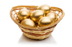 Golden eggs in a basket isolated on white background Royalty Free Stock Images