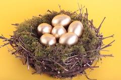 Golden eggs in bird nest over yellow Stock Photography