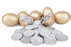 Golden eggs with coins. On white background Stock Photos
