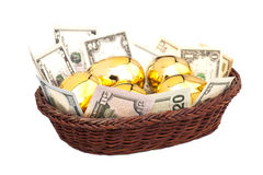 Golden eggs and dollars in basket Royalty Free Stock Images