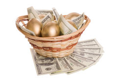 Golden eggs and dollars in a basket isolated Stock Photography