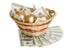 Golden eggs and dollars in a basket isolated Stock Image
