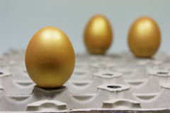 Golden eggs on an egg carton. Easter royalty free stock images
