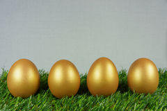 Golden eggs on a green. Four golden eggs on a green artificial turf stock photos