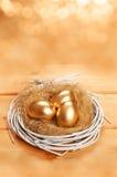 Golden eggs in the nest Stock Photo