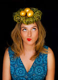 Golden eggs in the nest on the head of a woman Royalty Free Stock Photos