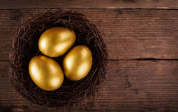 Golden eggs in the nest. Over wooden background with copy text Stock Photo