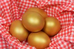Golden eggs in a patterned napkin. Five golden eggs in a patterned napkin stock photos