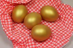 Golden eggs in a patterned napkin. Four golden eggs in a patterned napkin Stock Images