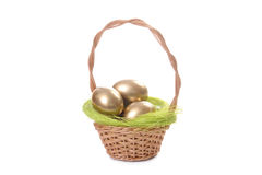 Golden eggs in wicker basket Royalty Free Stock Image