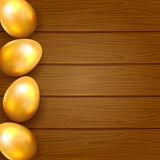 Golden eggs on wooden background Stock Image