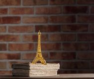 Golden Eiffel tower souvenir and old books. On wooden table at brick wall background. Library Stock Image