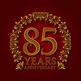 Golden emblem of eighty fifth years anniversary. Celebration patterned logotype with shadow on red.  Stock Photography