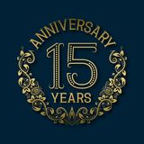 Golden emblem of fifteenth years anniversary. Celebration patterned logotype. With shadow on blue stock illustration