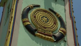 The golden emblem on a tower. A steady, low angle, extremely close up shot of a golden, circular emblem on a green tower stock footage