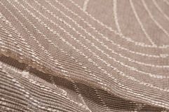 Golden embroidered textile. Golden curced stitches on mesh textile Royalty Free Stock Photo