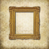 Golden empty frame on a grunge wall. Baroque empty frame on a grunge Victorian texture royalty free stock photography