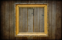 Golden empty frame on a wooden rustic wall Stock Images