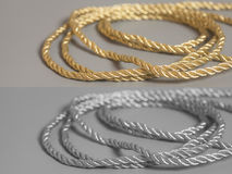 Golden end silver rope on gray Royalty Free Stock Images