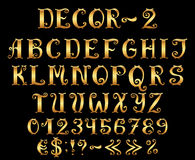 Golden english alphabet with numbers and symbols. Royalty Free Stock Photo