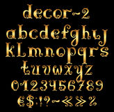 Golden english alphabet with numbers and symbols. Stock Images